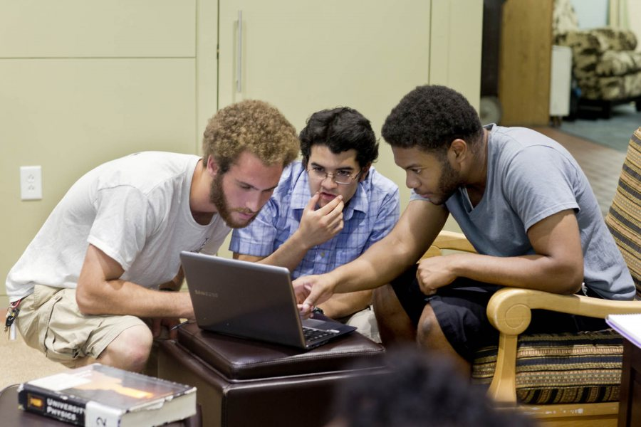 From left, physics major Dan Paseltiner '16 of Devon, Pa., physics major Javier Morales '16 of Guatemala City, and French major Kwamae Delva '18 of Conley, Ga. study and socialize in the Office of Intercultural Education. They were discussing anti-derivatives and integrals for a calculus course. (Phyllis Graber Jensen/Bates College)