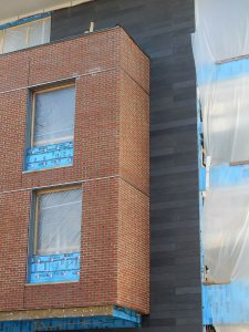 This image taken Oct. 20, 2015, shows contrasting masonry surfaces on a west wall of 65 Campus Ave.: brick and the rugged concrete paneling called Taktl. (Doug Hubley/Bates College)