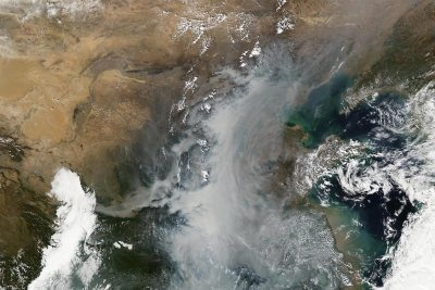 The milky white and gray at center of the image shows smog and fog event over China. The brighter whites at left and right are clouds. (NASA Earth Observatory)