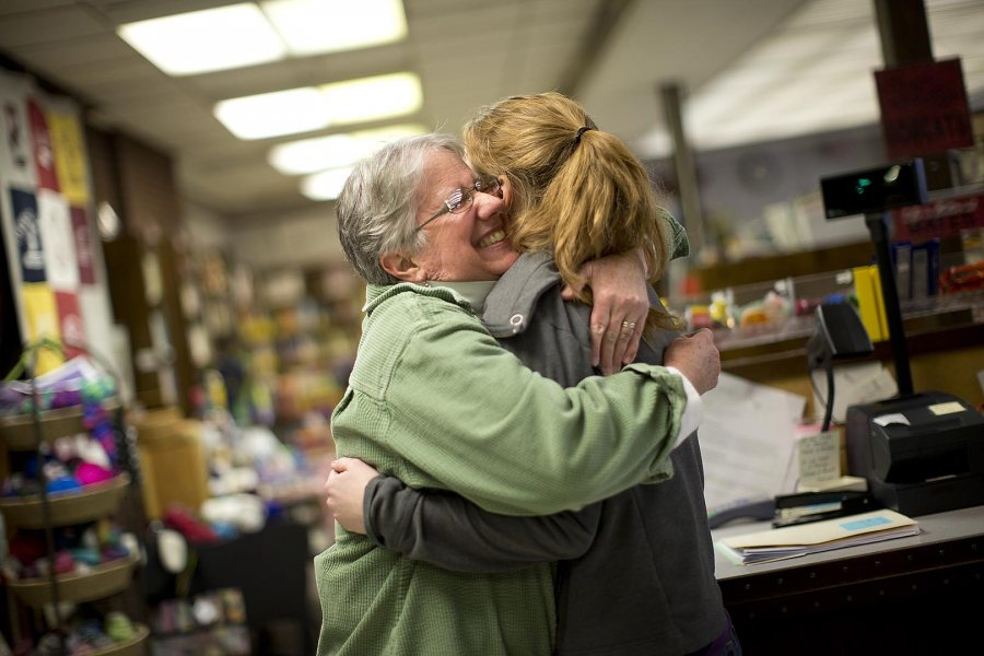 In March of her senior year at Bates, Hallie Balcomb '14 gets a hug from College Store director Sarah Potter '77. (Phyllis Graber Jensen/Bates College)