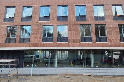 Storefront glass on the ground floor of 65 Campus Ave. reveals workers inside the building on Oct. 30, 2015. (Doug Hubley/Bates College)
