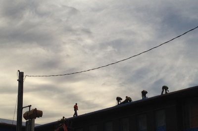 Workers for Industrial Roofing atop 65 Campus Ave. on Nov. 10, 2015. (Doug Hubley/Bates College)