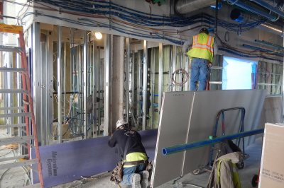 A drywall installer and an electrician fit out the fourth floor of 55 Campus Ave. on Dec. 1, 2015. (Doug Hubley/Bates College)