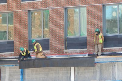 Technicians for Industrial Roofing Corp. install a weatherproof membrane on a shallow overhang at 65 Campus Ave. on Jan. 7, 2016. (Doug Hubley/Bates College)