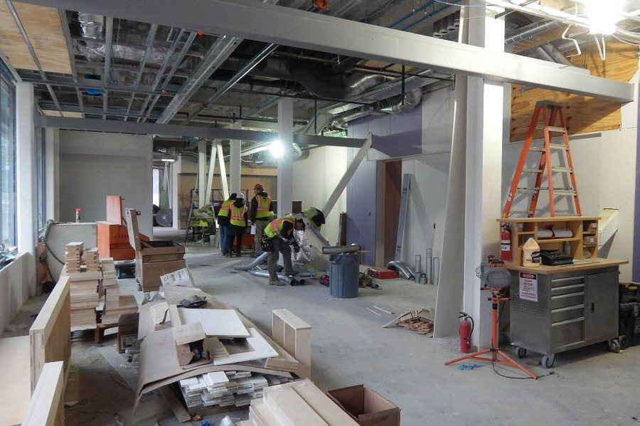 In store for Bates: While architects from the Ann Beha firm consult with a Consigli Construction executive, a ventilation technician cuts a piece of ductwork on Jan. 12, 2016. The Bates College Store will occupy this space in 55 Campus Ave. (Doug Hubley/Bates College)