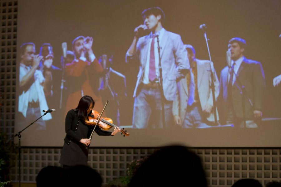 A projected image shows the late James Jhun '16 singing with his a cappella group as So Hee Ki '16 performs a work by Bach during the celebration of his life on Jan. 22. (Phyllis Graber Jensen/Bates