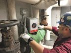 A worker installs Cut'nWrap modular and removable insulating product on a hot-pipe components in a Bates mechanical room. (Photo courtesy of Auburn Manufacturing Co.)