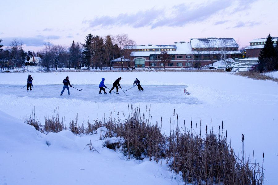 A group of Lewiston High School alumni home from college play afternoon pickup hockey game on the Puddle. (Phyllis Graber Jensen/Bates College)