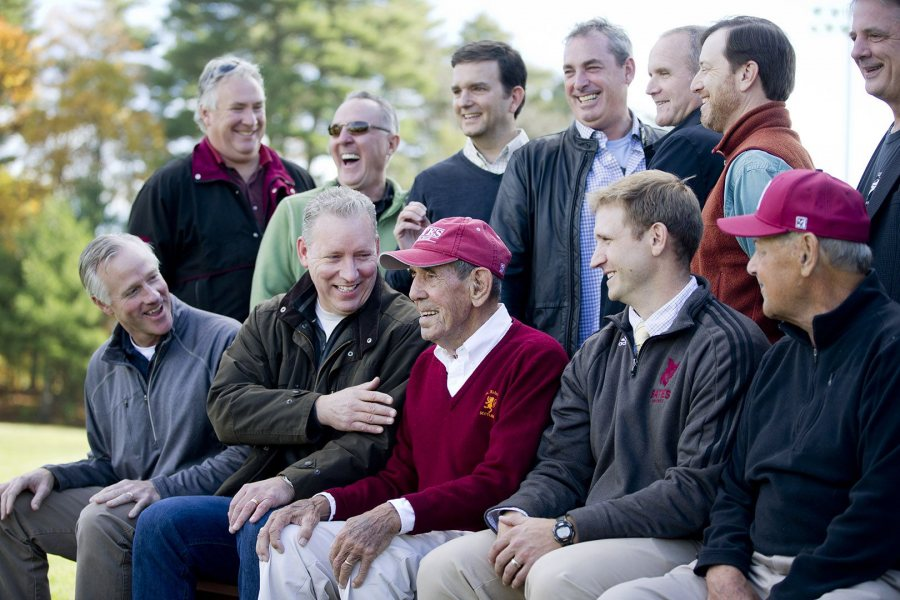 Chick Leahey '52 is surrounded by his former players, along with head coach Mike Leonard (second from right) and longtime assistant Bob Flynn (right) during a ceremony to retire Leahey's number 11 and dedicate a new hitting facility at Leahey Field. (Phyllis Graber Jensen/Bates College)