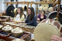 From left, Kinsey Moser'18 of Burke, Va.,  Jade Donaldson '18 of Wayne, N.J., and at rear,  Janet Bourne, postdoctoral fellow in the humanities and music lecturer, rehearse on one of Bates' two sets of gamelan instruments in the Olin Arts Center. (Phyllis Graber Jensen/Bates College)
