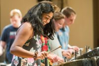 Zofia Ahmad '19 of Palo Alto, Calif. joins classmates for an encore at the Bates Steel Pan Orchestra concert.  The Bates Steel Pan Orchestra, under the direction of Duncan Hardy, performs traditional West Indies arrangements in the Olin Concert Hall on Monday, Dec. 7th 2015.