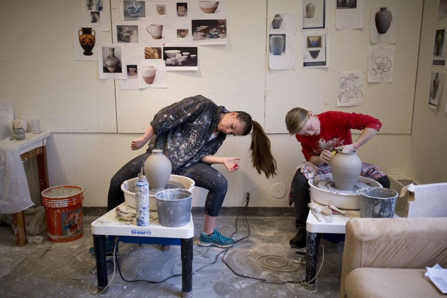 Studio art majors Sasha Lennon '16 (left) of Cape Elizabeth, Maine and Natalie Silver '16 of Bennington, Vt., throw pots in their Olin Arts Center studio in preparation for the Senior Thesis Exhibition. Lennon is double majoring in psychology, Silver in history. (Phyllis Graber Jensen/Bates College)