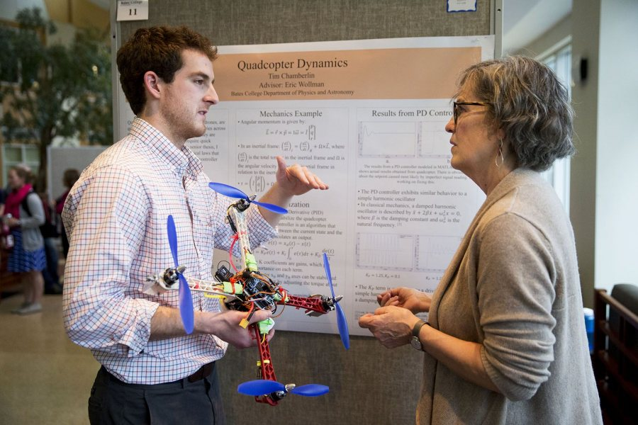 Tim Chamberlin '16 of Norwich, Vt., explains the physics behind drone flight to a listener who probably won't take flight: his mom, Kate Emlen. (Phyllis Graber Jensen/Bates College)