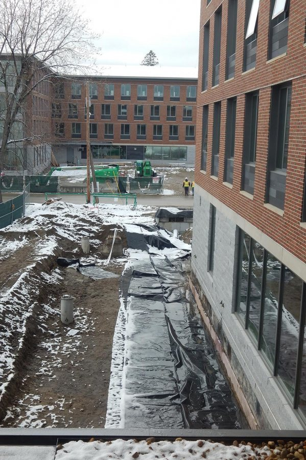 A rain garden seen from the second floor of 65 Campus Ave. on April 26, 2016. The plastic sheeting will divert runoff away from the foundation. The concrete cylinders at left are bases for light poles. (Doug Hubley/Bates College)