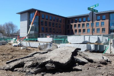 The old and the new: Remnants of an asphalt sidewalk are heaped in front of new granite curbs on April 27, 2015. In the background is 55 Campus Ave. (Doug Hubley/Bates College)