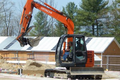 With the old boathouse in the background, an excavator moves dirt at the foundation site of the new boathouse. (Doug Hubley/Bates College)