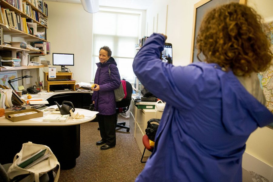 Tourse's' fact-finding visit included doumenting people in their campus spaces. Here, she videos Associate Professor of Politics Leslie Hill in her Pettengill Hall office. (Phyllis Graber Jensen/Bates College)