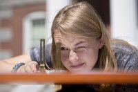 """A member of the """"Innovations in Mapping"""" class, Haley Crim '19 of Sandy Spring, Md., uses a surveyor's compass to determine an angle during a triangulation exercise on May 6, 2016. (Phyllis Graber Jensen/Bates College)"""