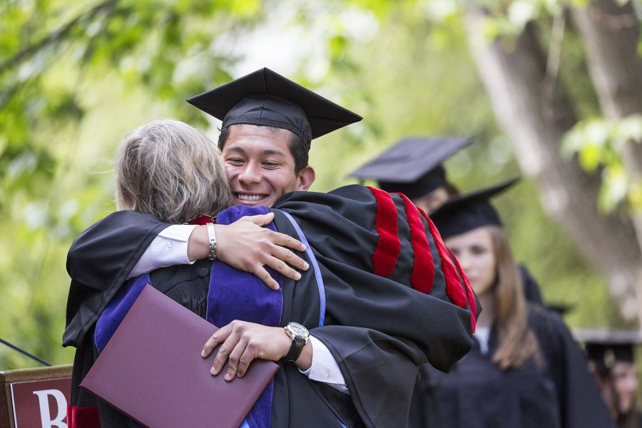 Norberto Diaz '16 of Carson, Calif., receives a hug and a diploma from President Spencer. (Josh Kuckens/Bates College)