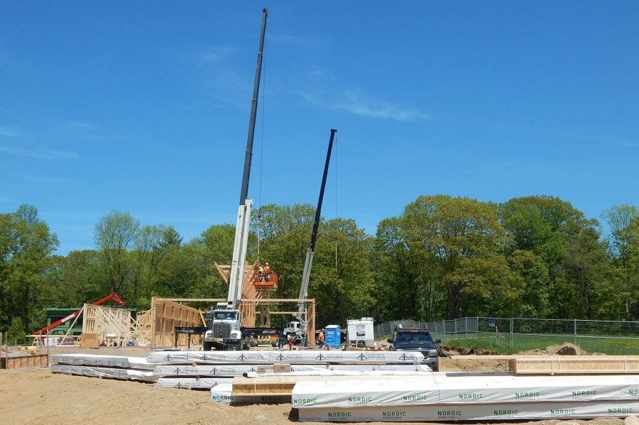 Two cranes help build the timber frame of Bates' new boathouse on May 26. (Doug Hubley/Bates College)