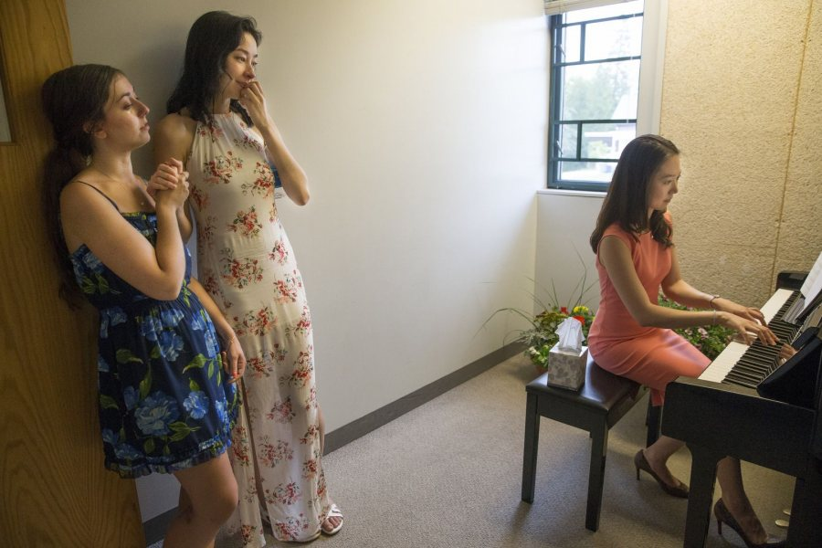 Iny Jhun, sister of the late James Jhun '16, plays a piano given to Bates by the James K. Jhun '16 Memorial Fund during a reception in Olin Arts Center hosted by the Jhun family. At left are James' friends Rebecca Schwartz '16 of West Hartford, Conn., and Amanda Zakowich '16 of Singapore. James, who died on Jan. 17, received a posthumous degree at Commencement. (Phyllis Graber Jensen/Bates College)