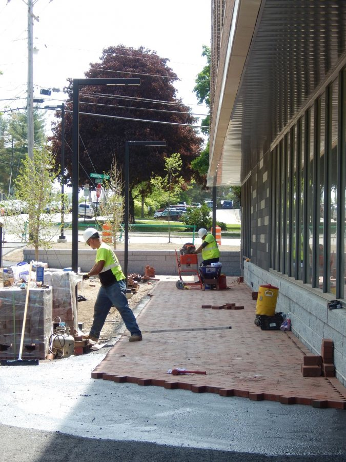 A new brick walkway at 65 Campus Ave. on May 31, 2016. The shiny stuff in the foreground is Karnak -- no relation to Johnny Carson, it's a sticky dilution of asphalt used to hold bricks in place. (Doug Hubley/Bates College)