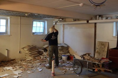 A worker scrapes tiles off the ceiling in the basement of Smith Hall on June 8, 2016. (Doug Hubley/Bates College)