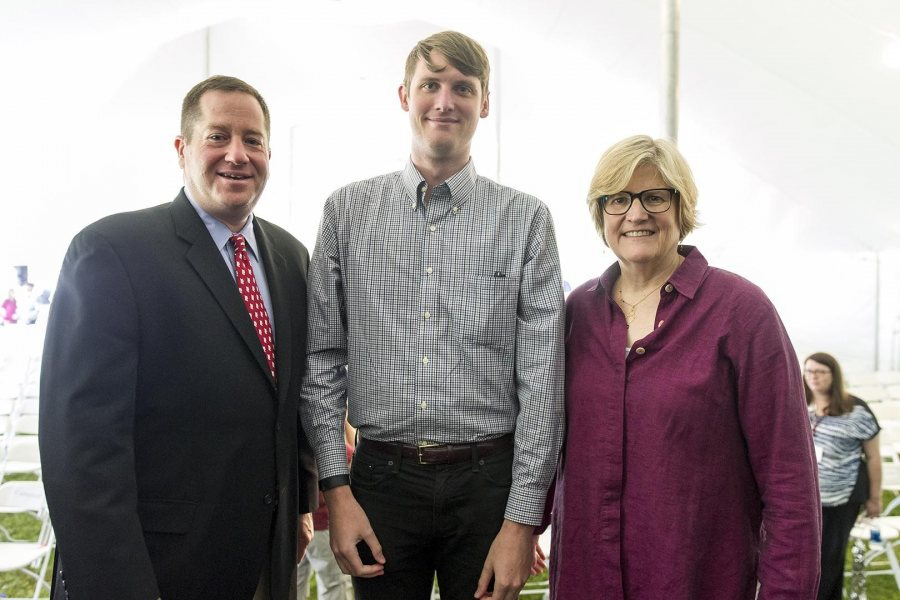 Bradley McGraw '10, recipient of the Distinguished Young Alumni Award at Reunion on June 12, poses with President of the Alumni Association Michael Lieber '92 and President of Bates College Clayton Spencer. (Josh Kuckens/Bates College)