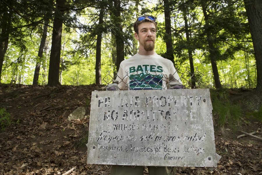 "Dana Cohen-Kaplan '16 holds an old sign that reads, ""Private Property: No Admittance Without Permission, Trespassers will be prosecuted, President and Trustees of Bates College, Owner."" (Phyllis Graber Jensen/Bates College)"