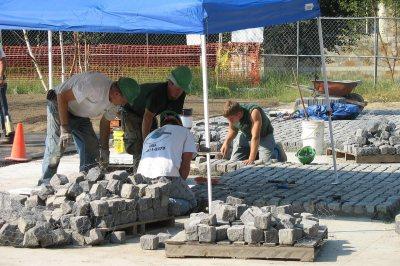 Masons setting cobblestones at the Alumni Walk entrance. (Doug Hubley/Bates College)