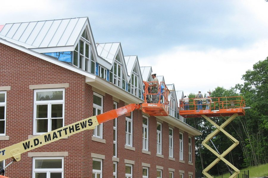 Wizards of oxide: Workers finish the gray-oxidized roofing on the west side of the new student housing. (Doug Hubley/Bates College)