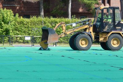 Like a giant pizza cutter, the circular blade on this front-end loader is slicing the Campus Avenue Field AstroTurf on July 6, 2016, prior to rolling it up for removal. (Doug Hubley/Bates College)