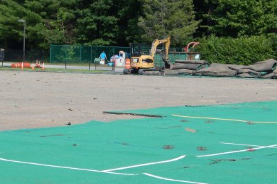 With some of the AstroTurf still in place on Campus Avenue Field, an excavator stacks rolls of the turf that have just been peeled off on July 6, 2016. (Doug Hubley/Bates College)