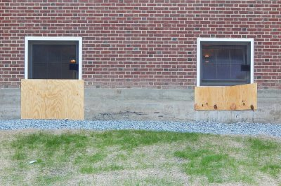The plywood is covering openings where wall material was removed to enlarge the windows on the back side of Smith Hall. (Doug Hubley/Bates College)