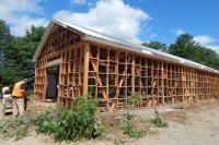Carpenters for R.S. Egenstafer Construction of Littleton, Maine, dismantling the old Bates boathouse on July 19, 2016. (Doug Hubley/Bates College)