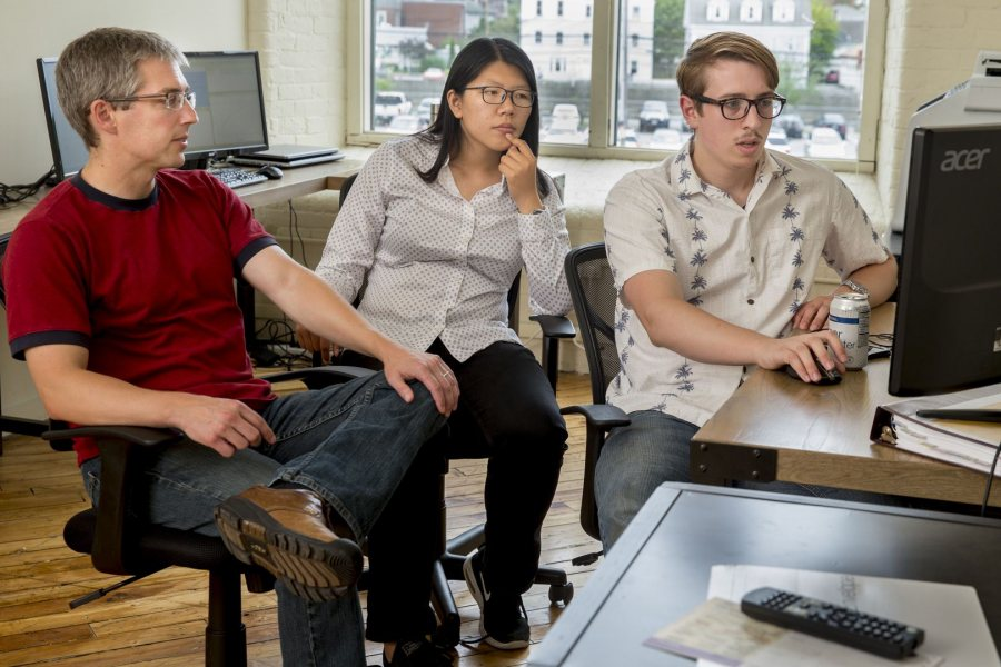 From left, Associate Professor of Economics Nathan Tefft meets with his Purposeful Work interns Fan Dong '17 of Beijing and Michael Varner '17 of Chelsea, Mich, in the offices of Looking Glass Investments in the Fort Andross Mill in Brunswick. Tefft is executive vice president and chief economist for LGI, a firm that invests in peer-to-peer lending. (Phyllis Graber Jensen/Bates College)