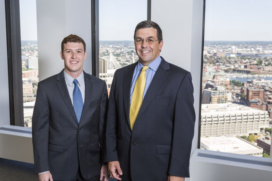 "Mike Mulach '17 of Rocky River, Ohio, poses with his mentor, Brad Adams '92, during his Purposeful Work internship at TM Capital in Boston. In learning about mergers and acquisitions, Mulach says that ""there's no paper pushing here. I'm doing everything a full-time person would do."" (Josh Kuckens/Bates College)"