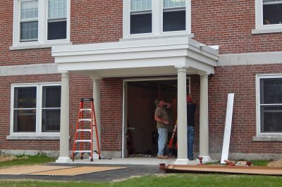 Workers install the door unit at the new rear entrance to Wentworth Adams Hall on Aug. 10, 2016. (Doug Hubley/Bates College)