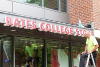A technician for Exposé Signs & Graphics has just finished mounting a sign for the College Store on a front canopy at 65 Campus Ave.  (Doug Hubley/Bates College)