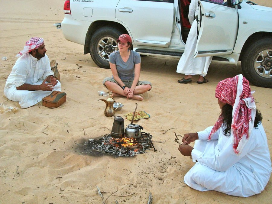 During the 2012 Short Term to Saudi Arabia, anthropology major Devin Tatro '14 talks with Saudi men during an outing to a desert farm in the Eastern Province. At the gathering, the Bates women got permission not to wear their abayas. (Photograph by Ana Bisaillon '12)