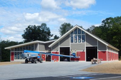 Painters were finishing up the exterior of Bates' new boathouse on Aug. 30, 2016. (Doug Hubley/Bates College)