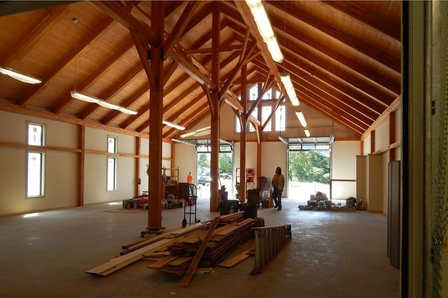 """""""It's a cathedral,"""" says rowing coach Peter Steenstra: The boat storage area in the boathouse. The wood on the floor was recovered from Bates' old boathouse for decorative use in the new facility. (Doug Hubley/Bates College)"""