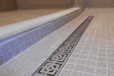 In the new and improved Smith Hall showers, fancy metalwork decorates the drain troughs and a tiled barrier ensures that bathers don't have to stand in each others' runoff. (Doug Hubley/Bates College)