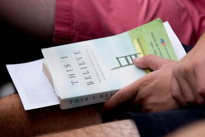 "A first-year student holds a copy of the Common Reading assigned to the Class of 2020. Dan Gediman, co-editor of the ""This I Believe"" books and executive producer of NPR's ""This I Believe"" radio program, delivered the Convocation address on Sept. 6. (Phyllis Graber Jensen/Bates College)"