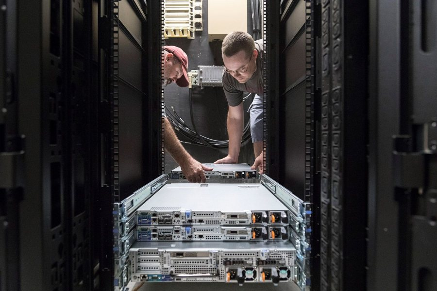 Network Infrastructure Project Manager Kevin Poland, left, and Desktop Operations Analyst Matthew Thomas install components of Bates' new High Performance Computing Cluster at 65 Campus Ave. New members of the physics faculty have taken the lead in bringing the system to Bates. (Josh Kuckens/Bates College)