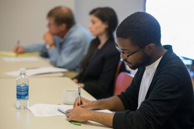 Jeremy Glover '17 of Cleveland Heights, Ohio, takes notes during the New Approaches to Early Modern Literature and Culture symposium held at Bates on Sept. 26. In the background are Senior Lecturer in English Rob Farnsworth and Roya Biggie of Grinnell College. (Phyllis Graber Jensen/Bates College)