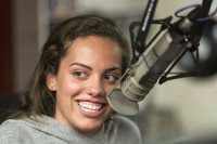 Olivia Bell '19 laughs with her co-hosts as she delivers a promotion.