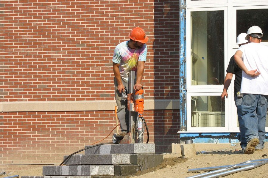 Taken for granite: A worker drills a hole in stone steps for a handrail at the new student housing. (Doug Hubley/Bates College)