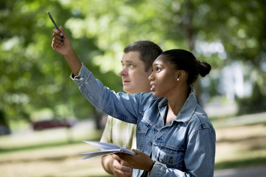 """On the Historic Quad, Assistant Professor of Biology Brett Hugget teaches basic techniques to observe and document natural life to Paige Rabb '20 of Stamford, Conn., a student in the First Year Seminar """"The Natural History of Maine's Neighborhoods and Woods."""" (Phyllis Graber Jensen/Bates College)"""