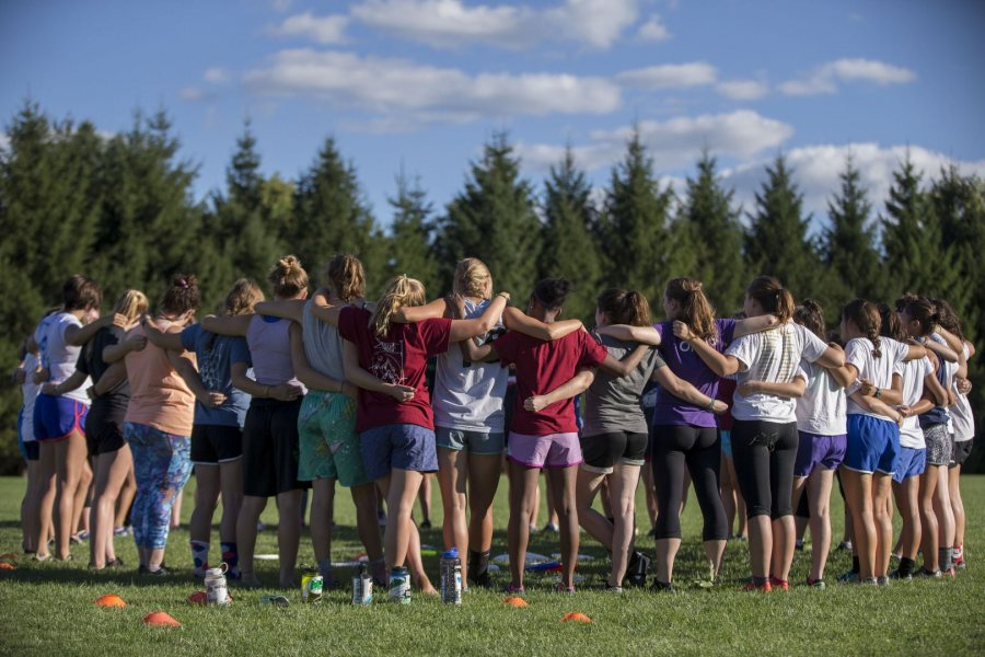 The women's ultimate team huddles for announcements at the beginning of practice on the softball field. (Phyllis Graber Jensen/Bates College)